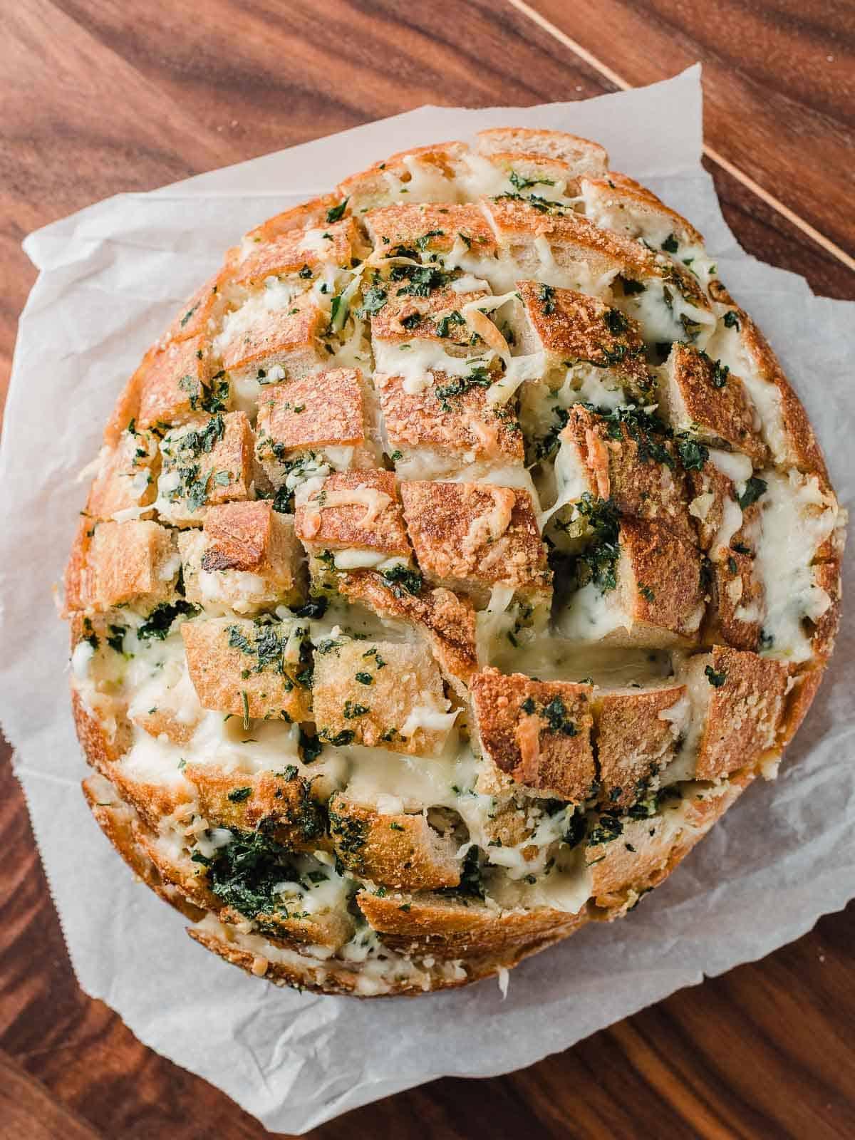 Pull apart garlic cheese bread on a cutting board.
