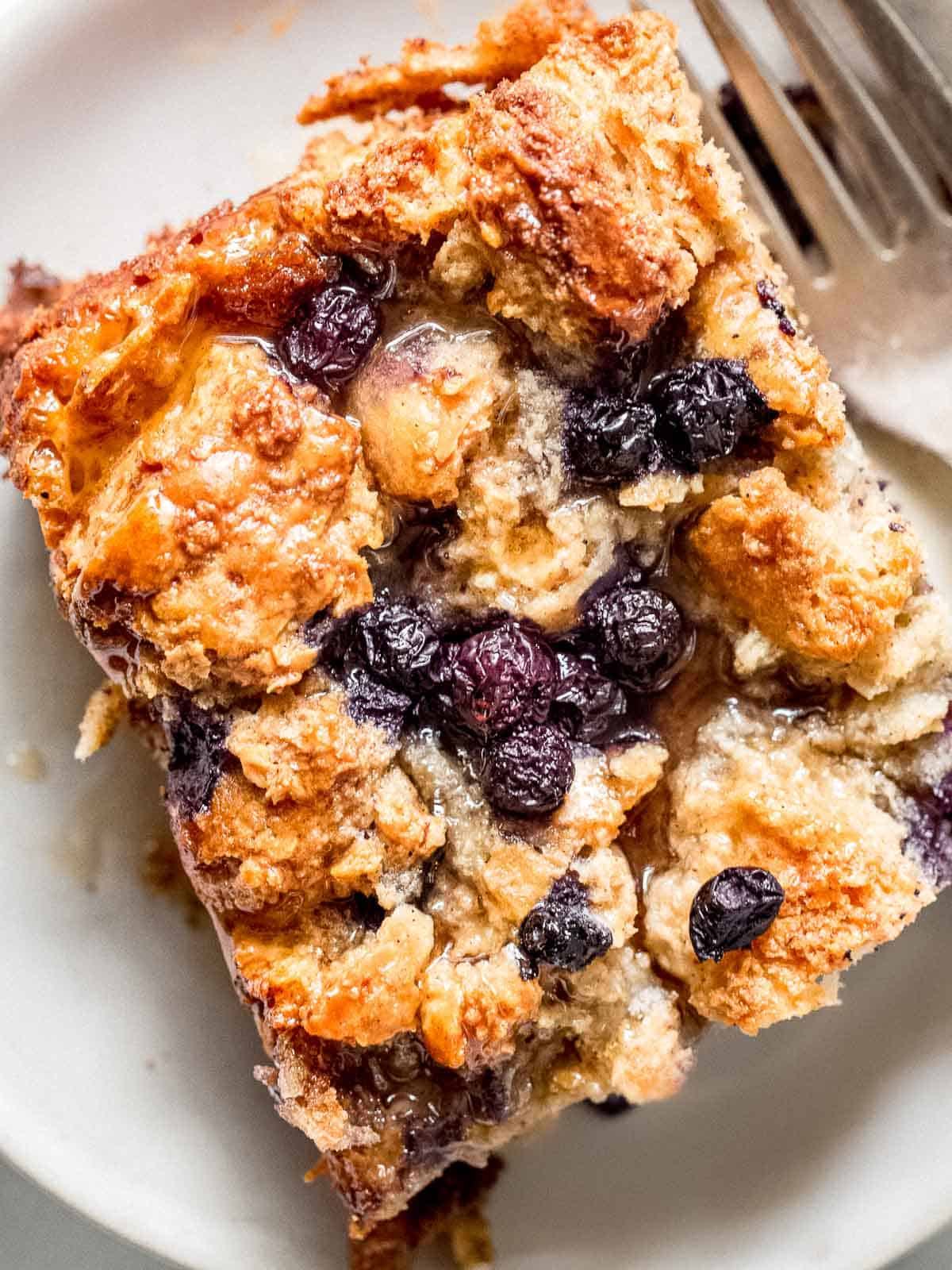 A slice of blueberry bread pudding on a plate.