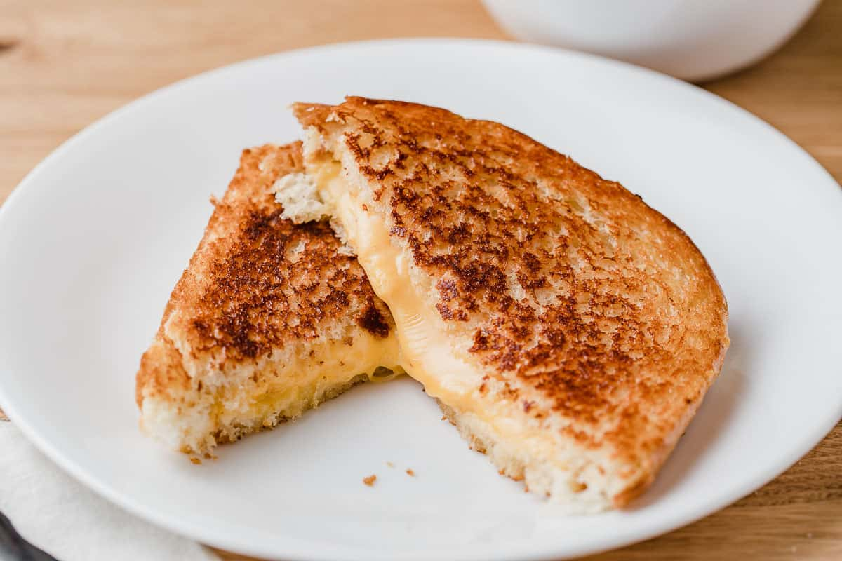 A hot grilled cheese sandwich on a plate cut in half.