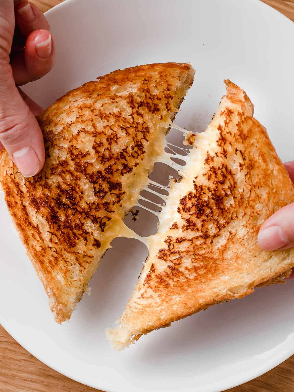 A grilled cheese sandwich cut in half being pulled apart with melted cheese.