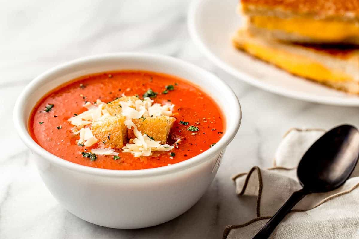 Homemade tomato soup in a bowl with cheese and croutons.