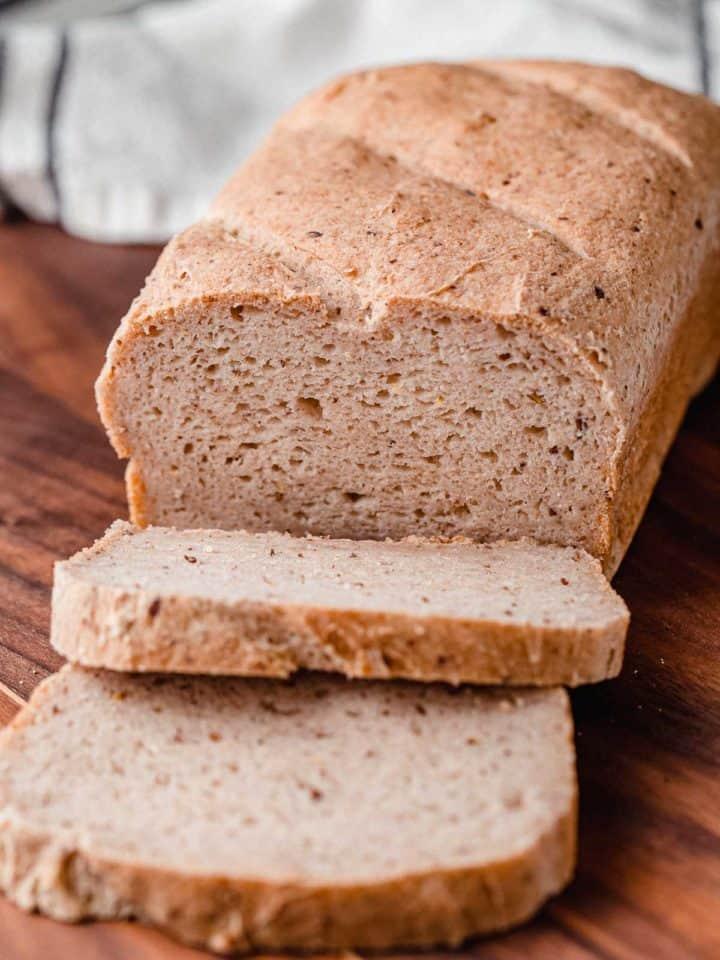 A loaf of gluten free sourdough bread on a cutting board.