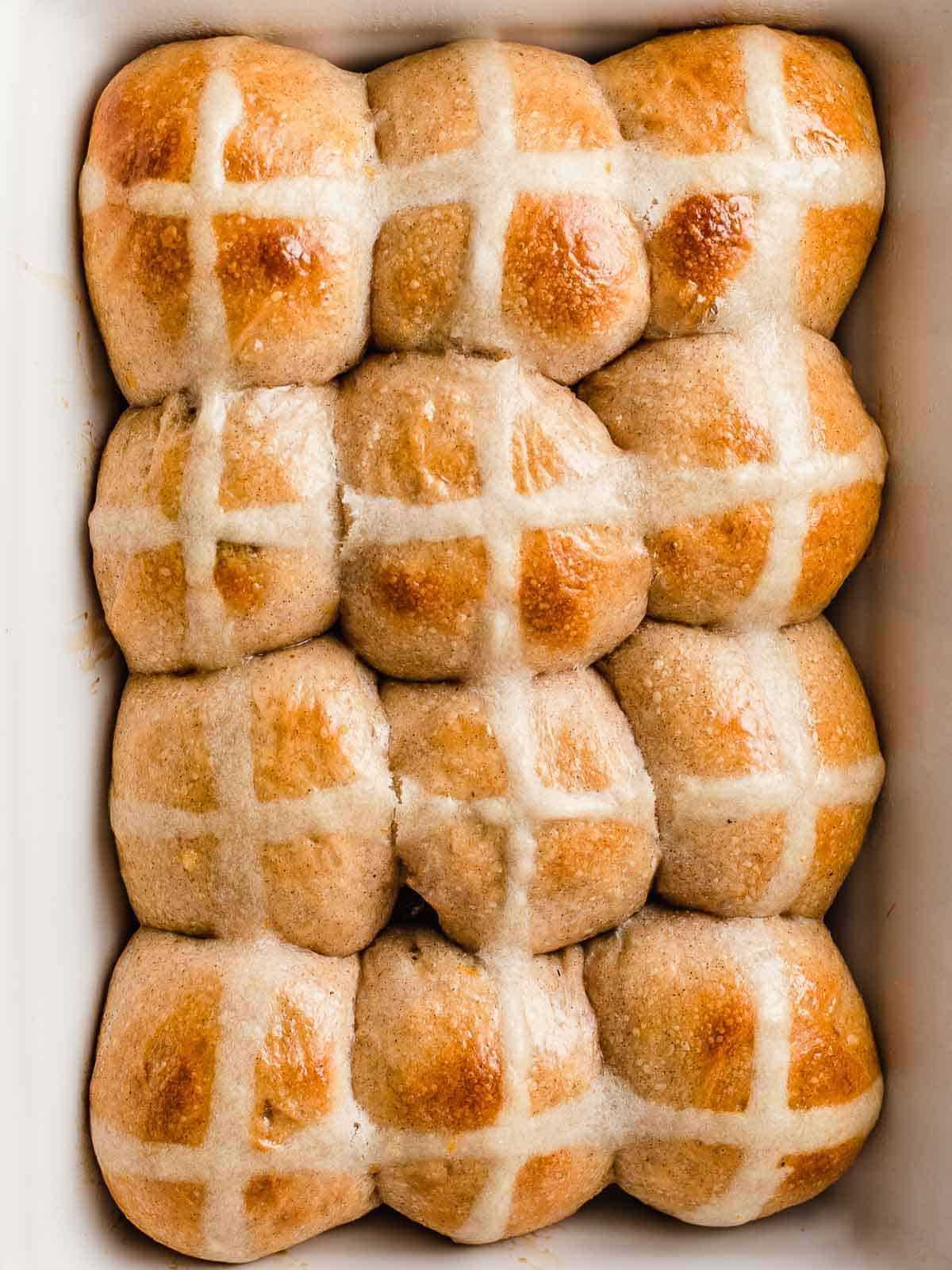 Sourdough hot cross buns in a baking dish.