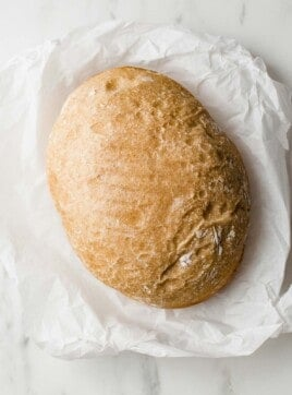 A loaf of slow cooker sourdough bread on a piece of parchment paper.