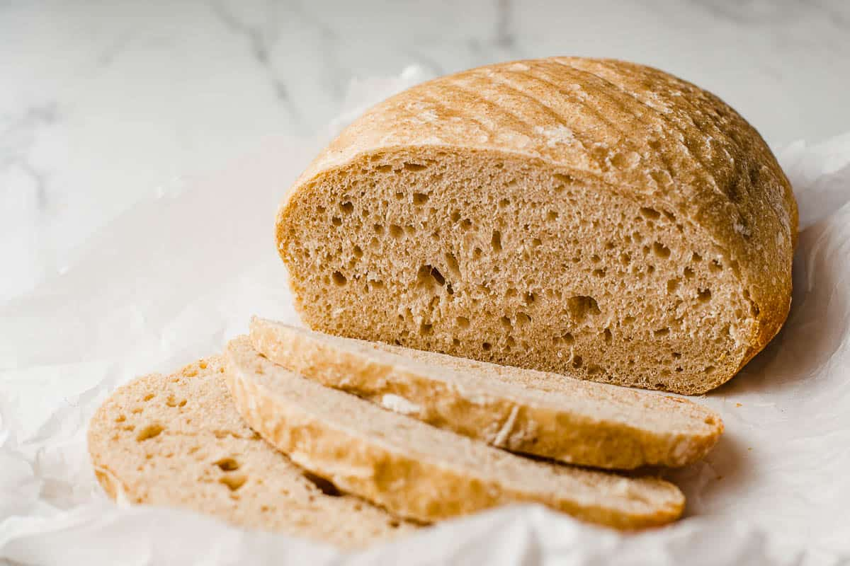 A sliced loaf of slow cooker sourdough bread on a piece of parchment paper.