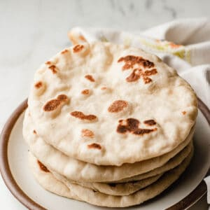 Sourdough naan stacked on a plate.