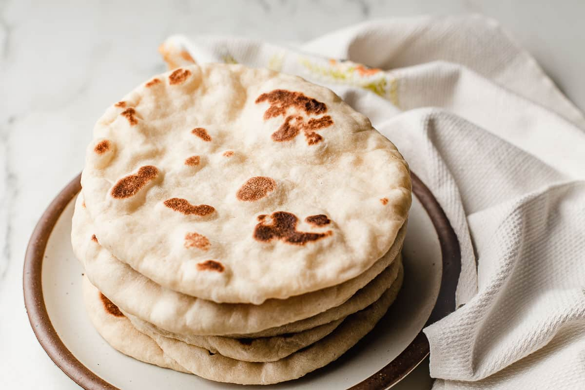 A plate of sourdough naan on a table.