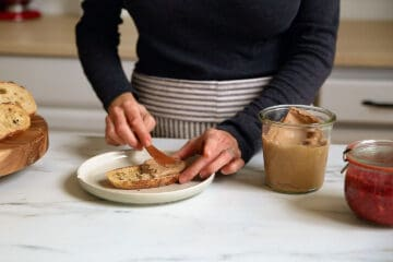 A person spreading almond butter onto toast.