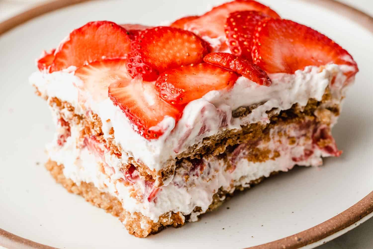 A slice of strawberry icebox cake on a plate.