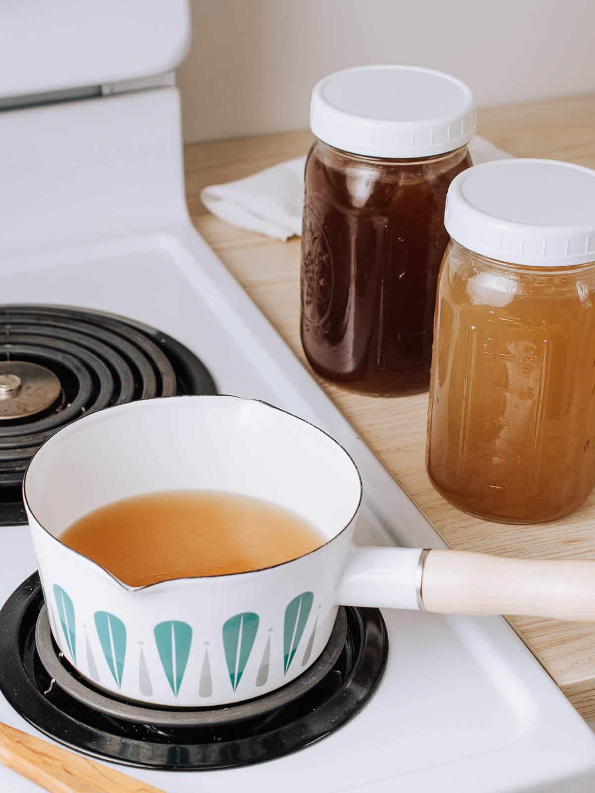 Chicken bone broth warming on the stovetop.
