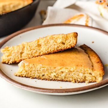 Two slices of cornbread on a plate.
