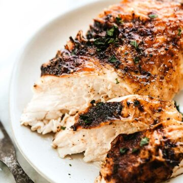 A slice of juicy chicken breast on a plate.