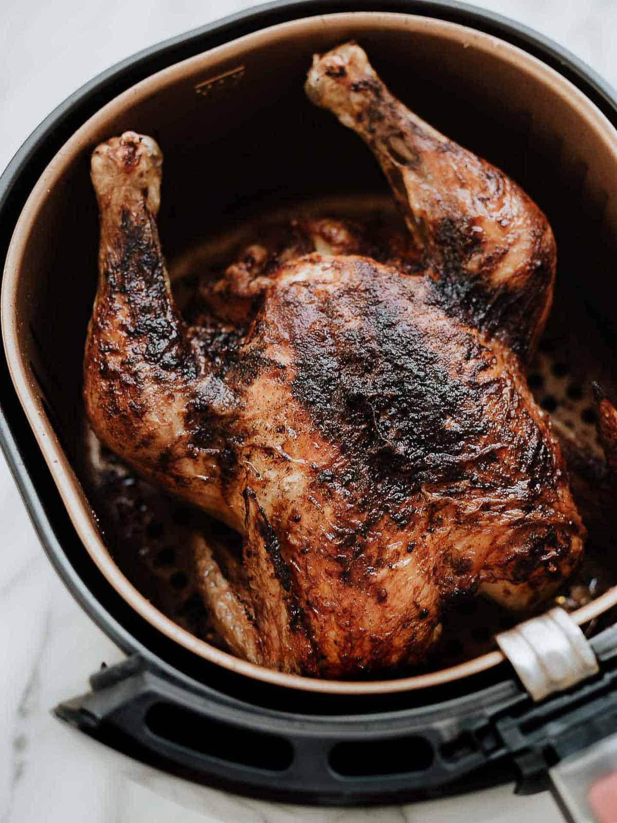Air fryer whole chicken in the basket.