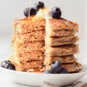 A stack of pancakes with blueberries and syrup.