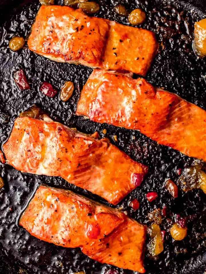 Salmon in a skillet glazed with mango chutney.
