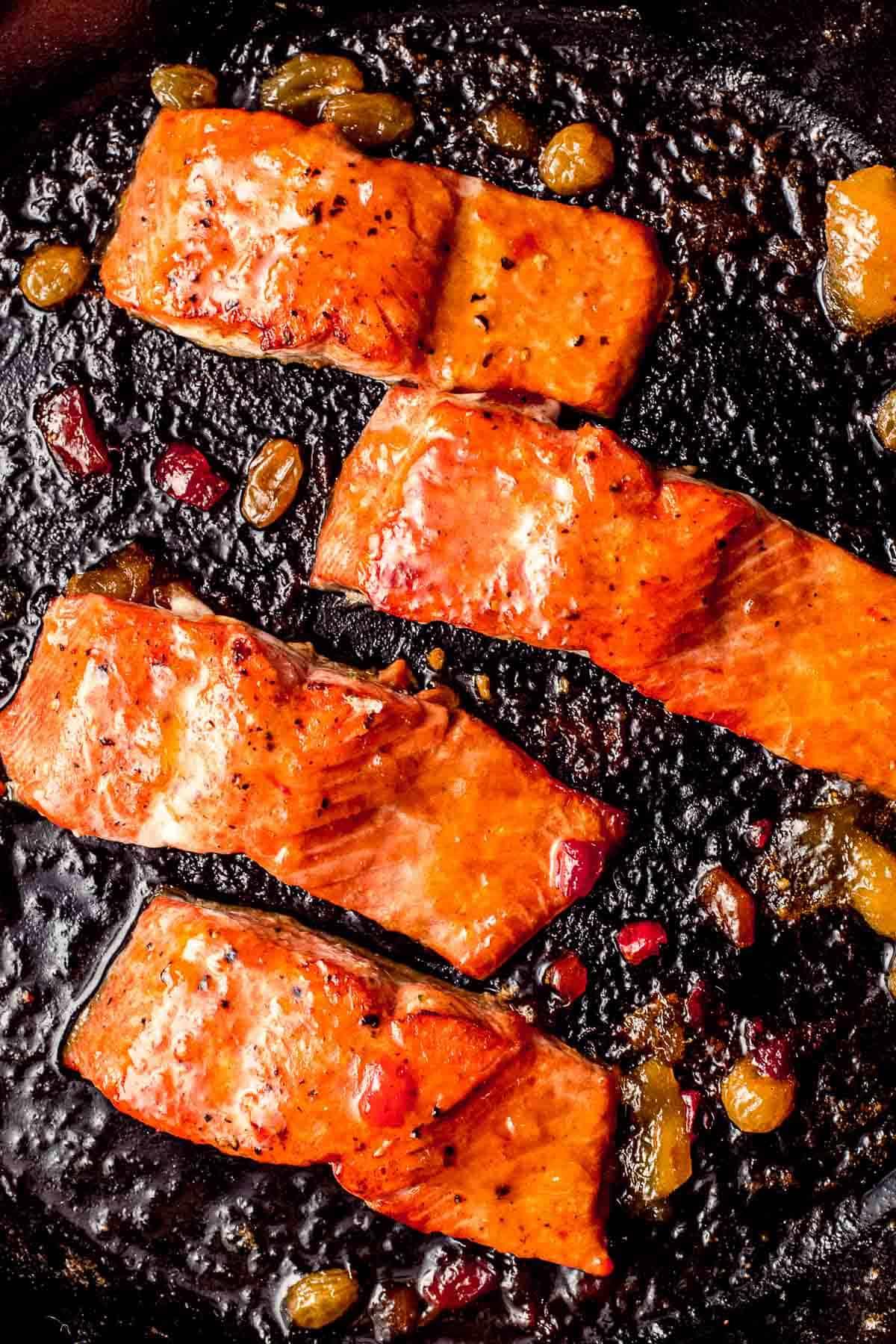 Four pieces of salmon in a skillet glazed with mango chutney.