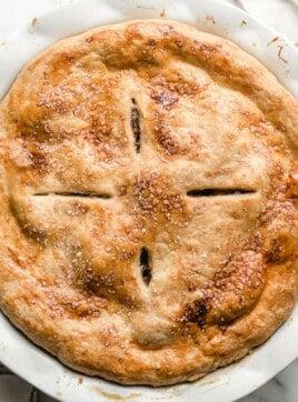 A top view of a pie crust in a pie plate on a table.