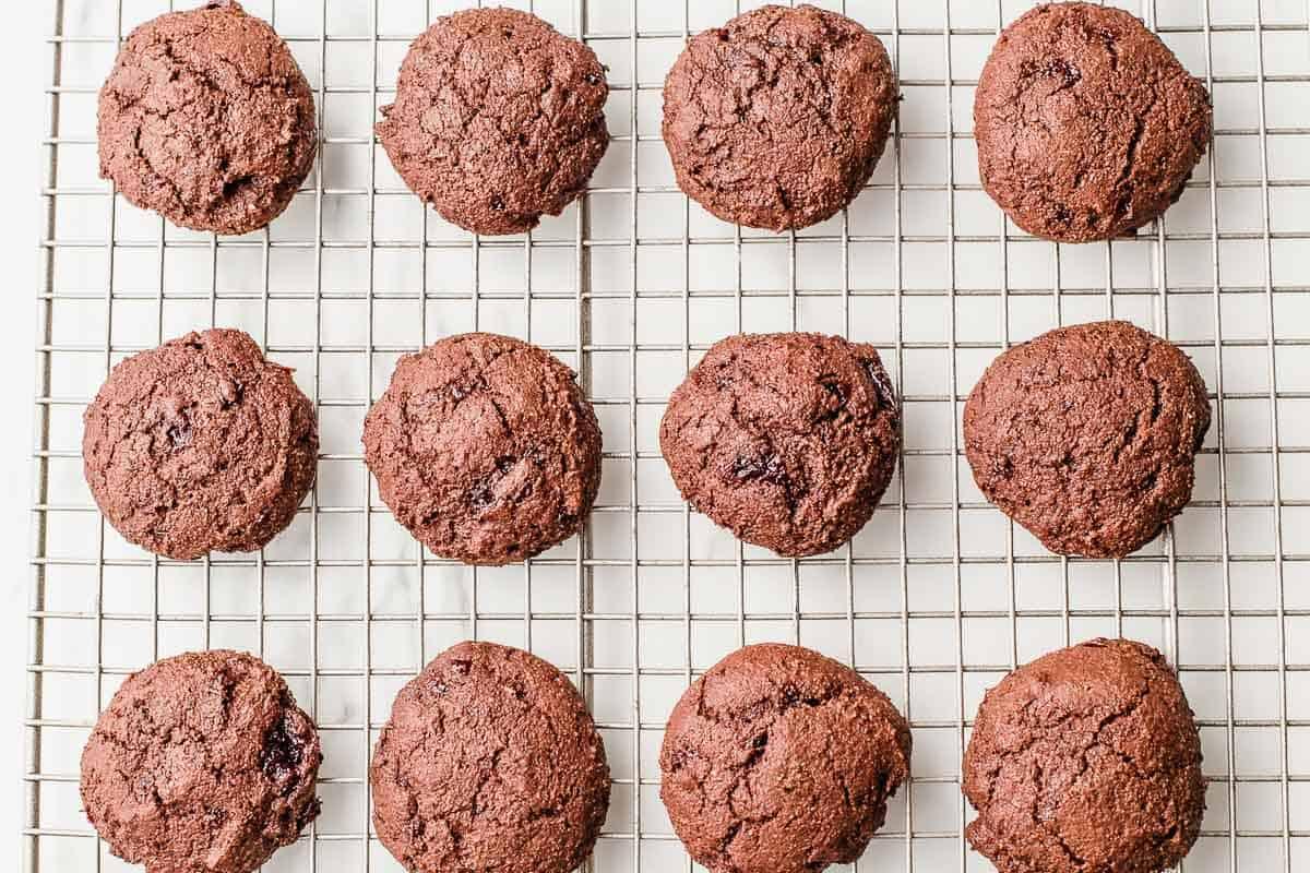Chocolate cherry jam cookies on cooling rack.