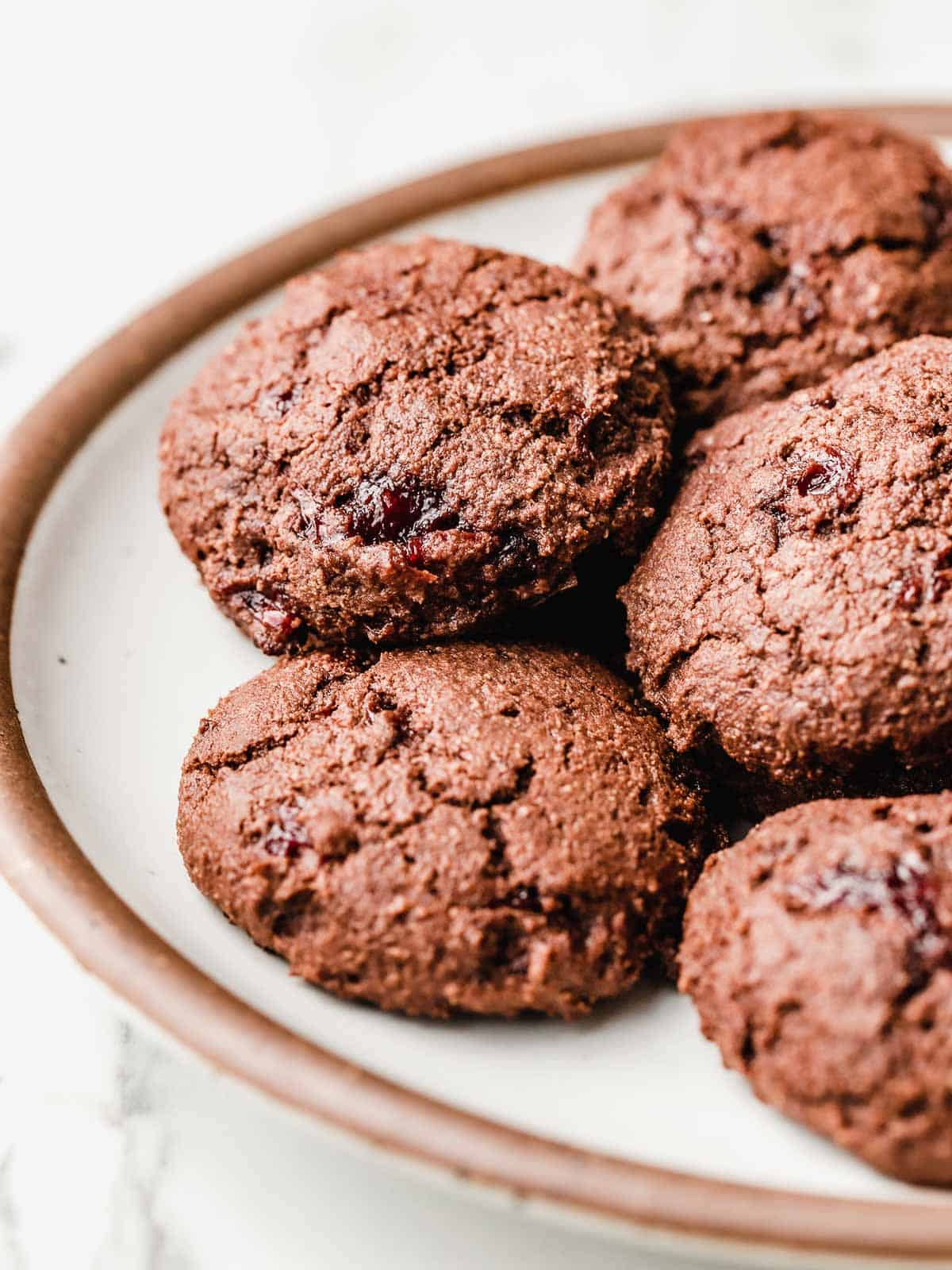 Chocolate cherry jam cookies on a plate.