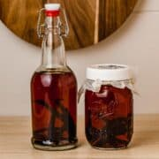 Two jars of homemade vanilla extract on a counter.