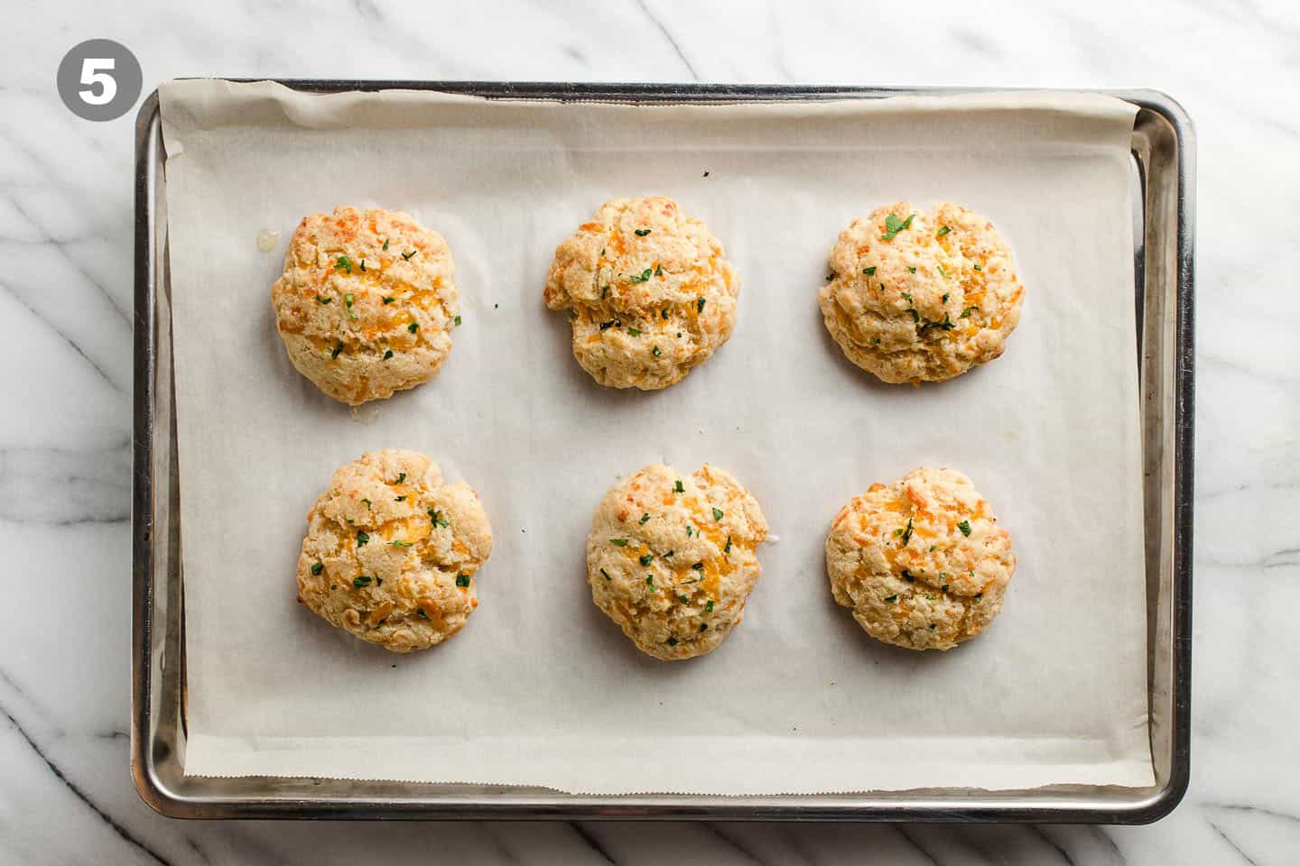 Baked cheddar bay biscuits on a baking sheet.