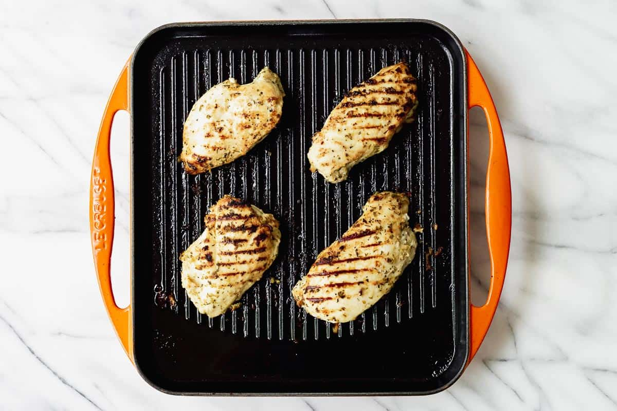 Four chicken breasts on a grill pan.