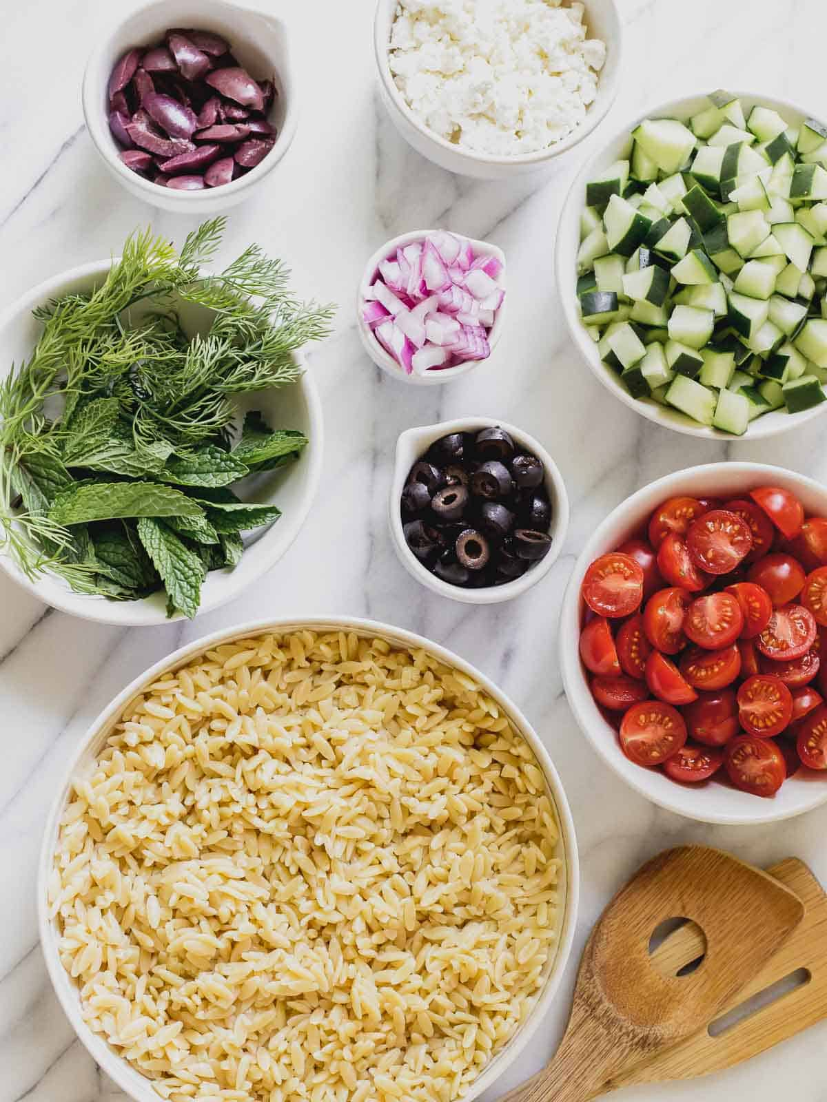 Greek orzo salad recipe ingredients on a table.