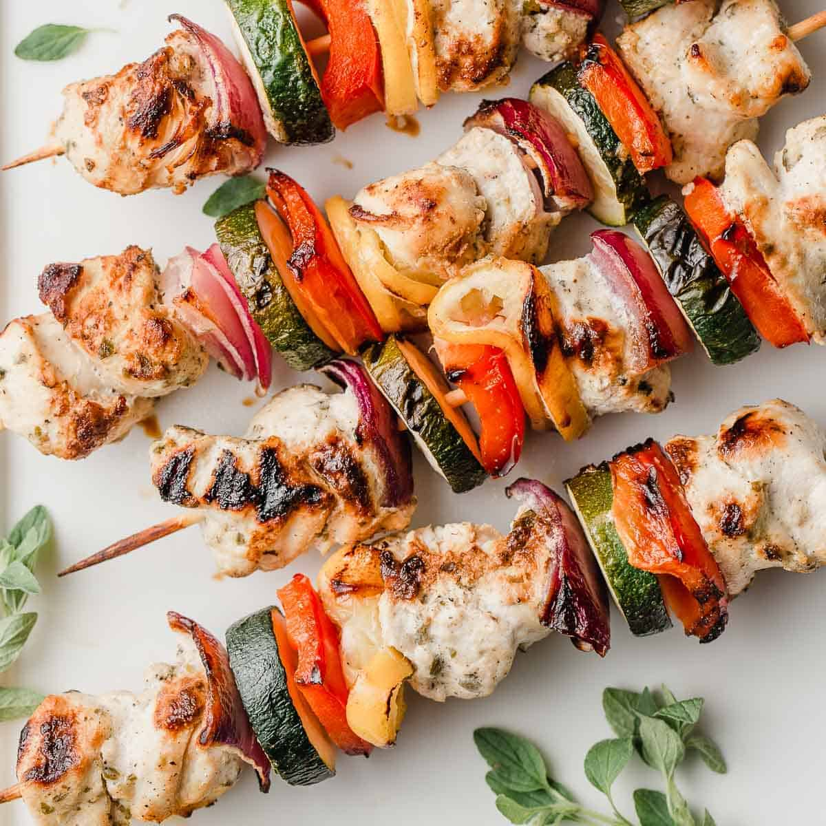 Homemade greek chicken kabobs on a serving platter.