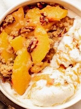 Peach crisp in a bowl with ice cream.