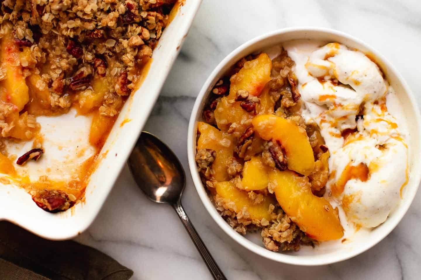 A bowl of peach crisp with ice cream next to the baking dish.