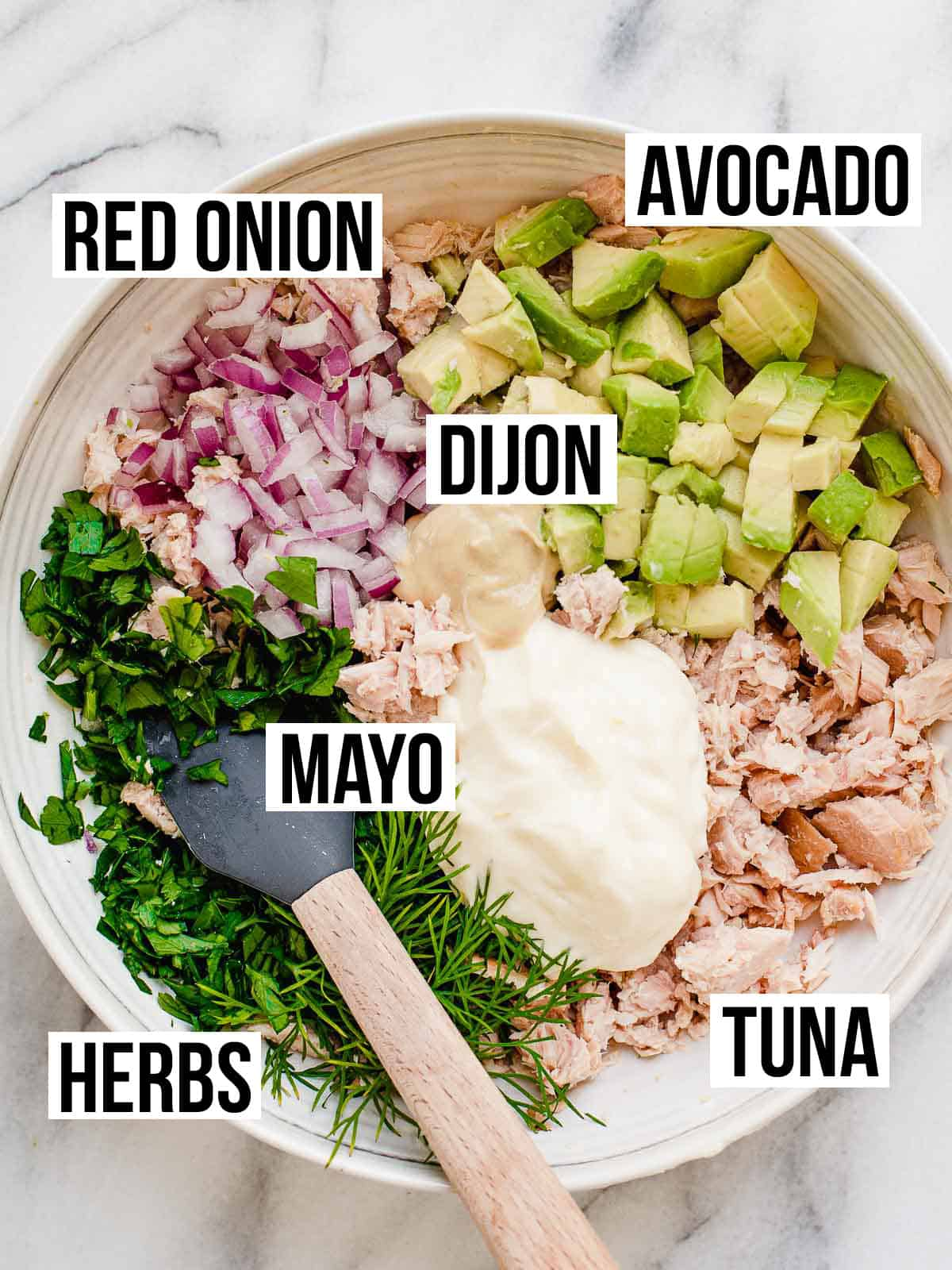 Tuna salad ingredients in a bowl with a spatula.
