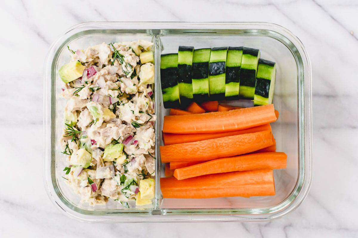 Tuna salad, carrots and cucumber slices in a meal prep container.