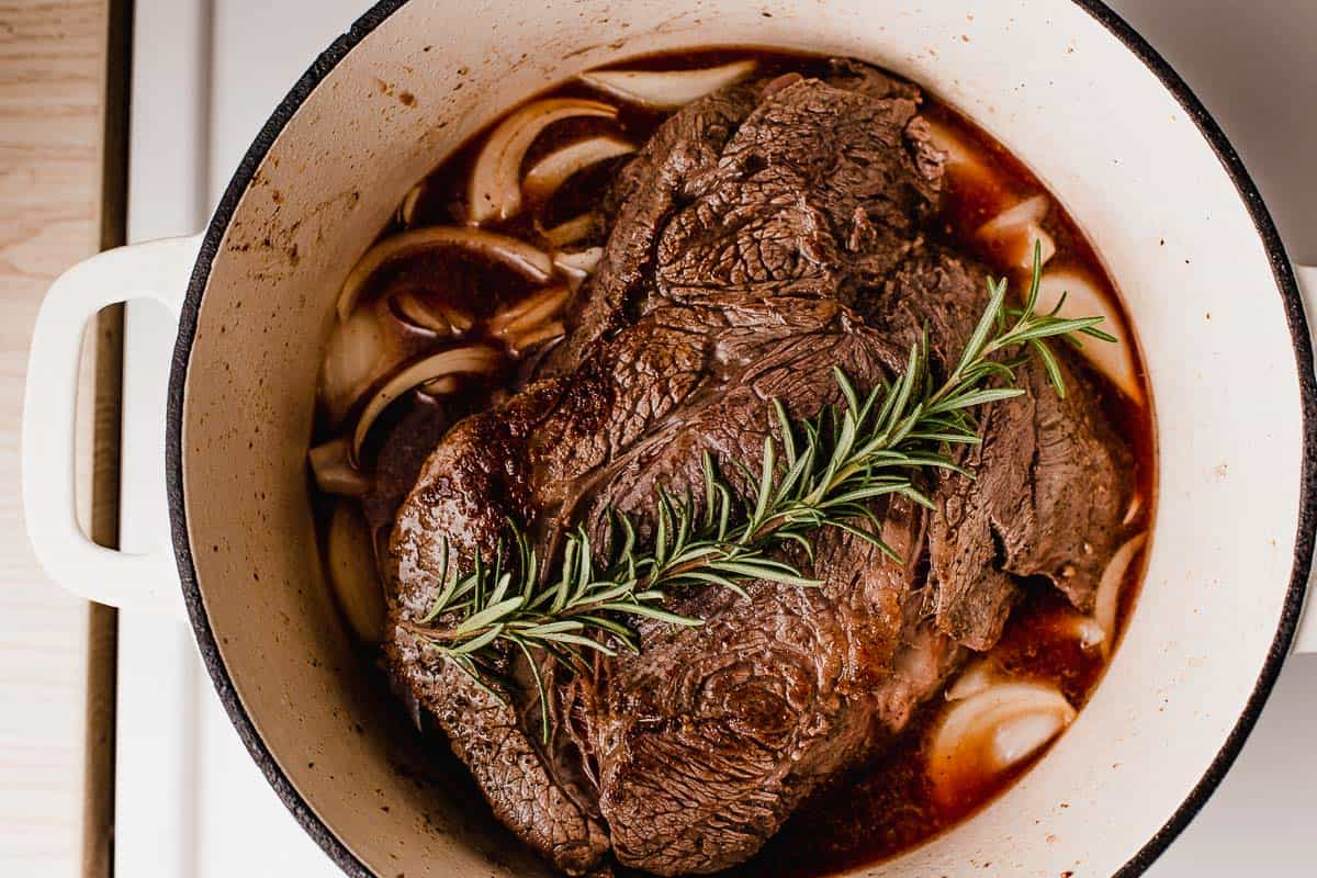 A chuck roast with onions and rosemary before going in the oven.