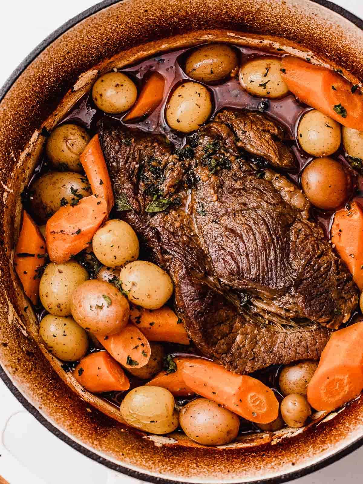 A classic pot roast in a dutch oven with veggies.