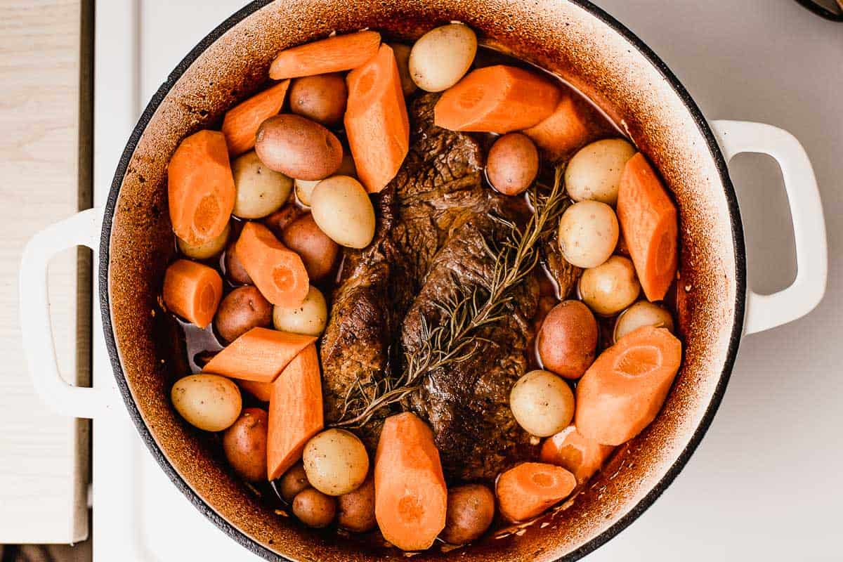 Adding carrots and potatoes to the pot roast.