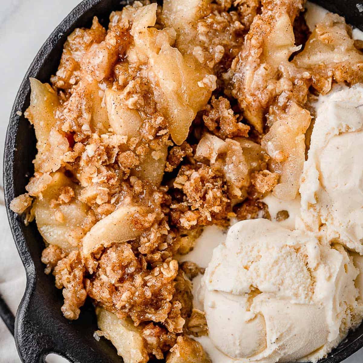 Apple crisp in a bowl with vanilla ice cream.