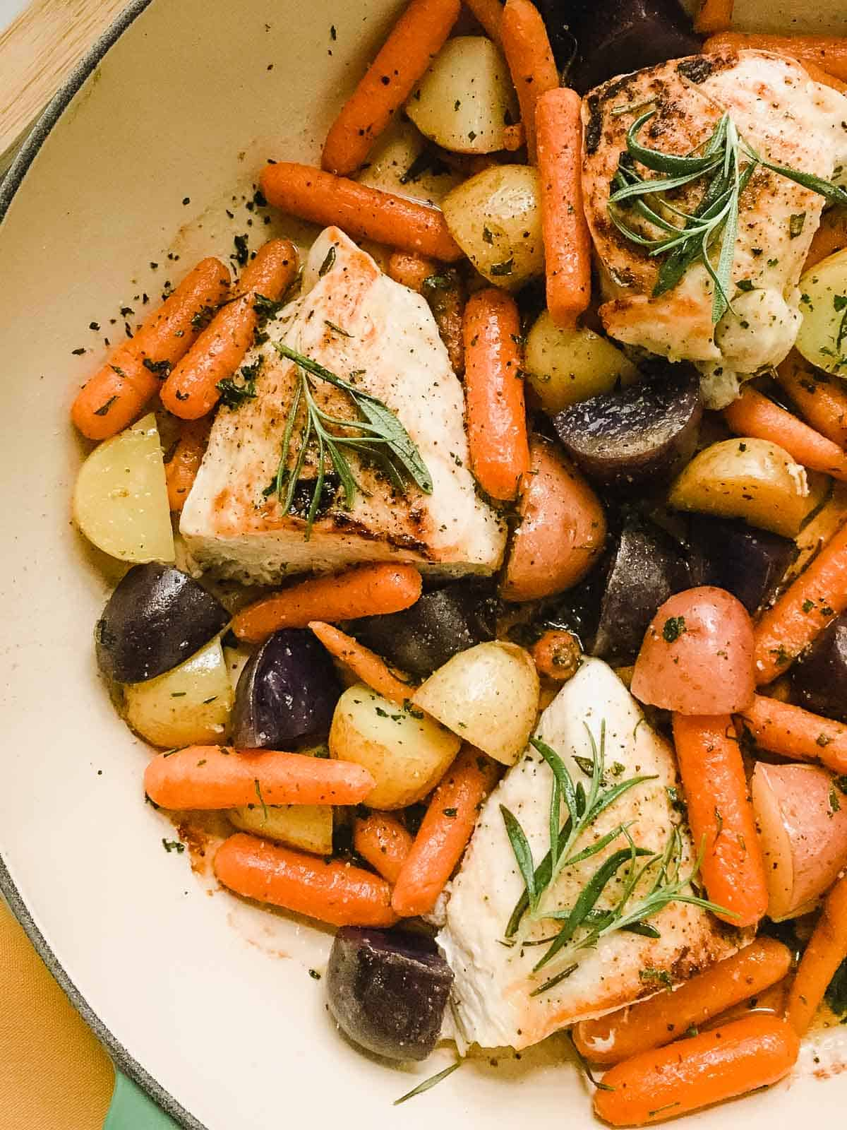 Closeup photo of rosemary chicken with potatoes and carrots.