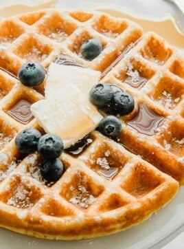 A gluten free waffle on a plate with butter and syrup.