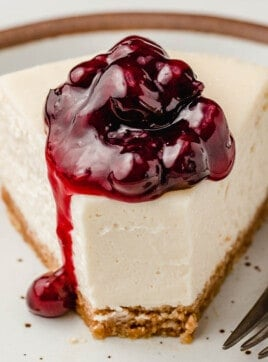 A slice of cheesecake with blueberry topping on a plate.