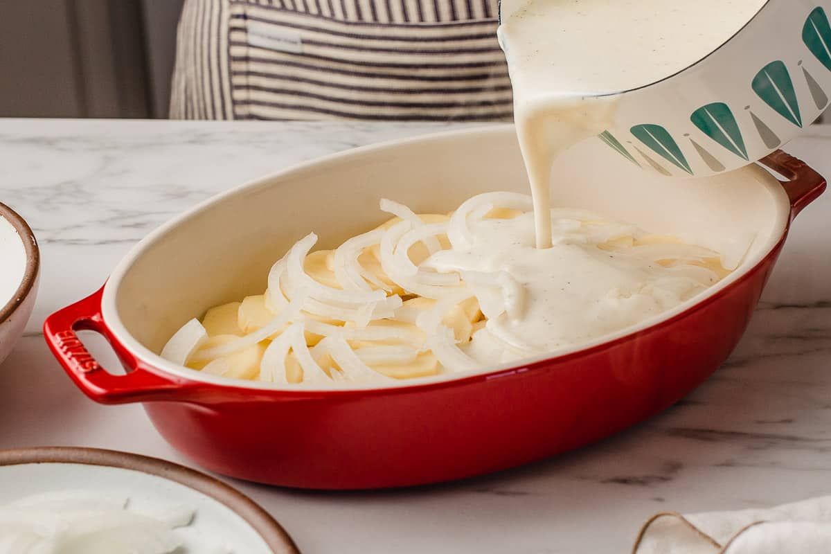 Pouring cream sauce over the first layer of scalloped potatoes.