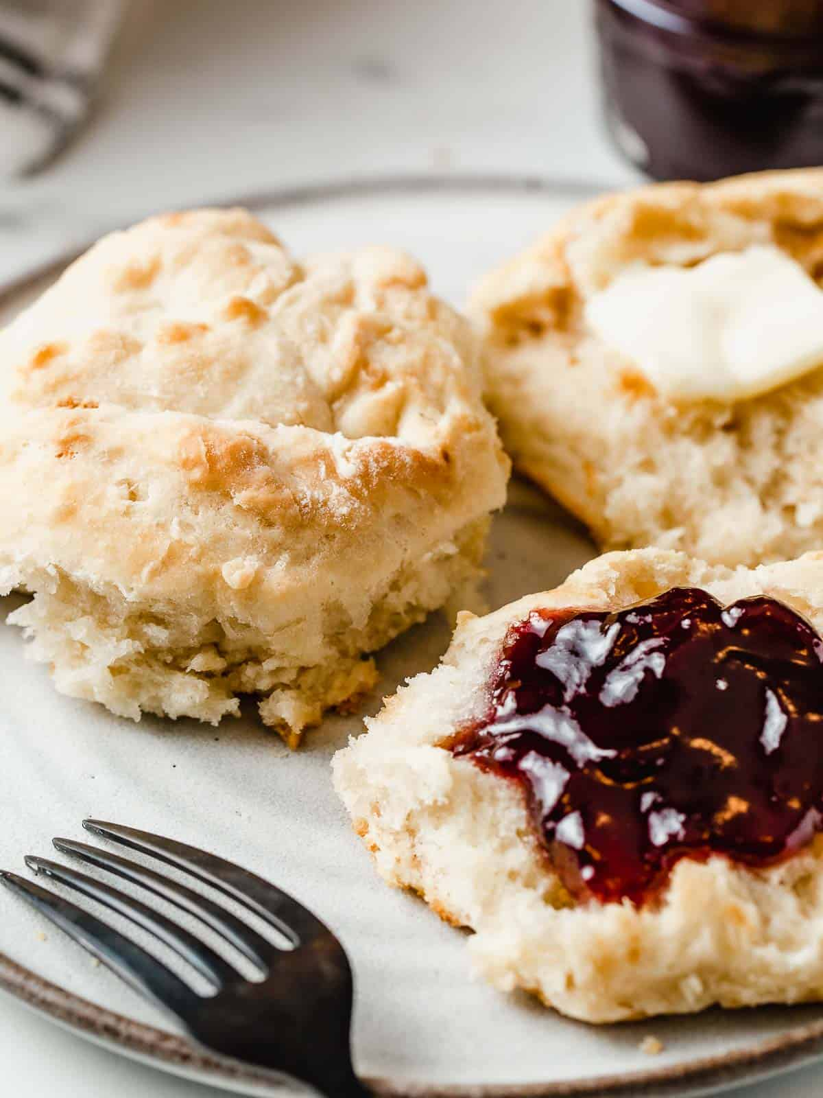 Sourdough biscuits with butter and jam in a plate.