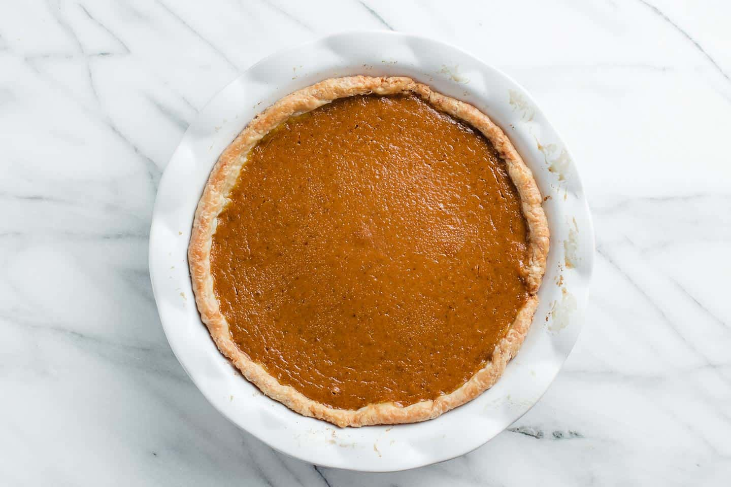 A baked pumpkin pie cooling on the counter.