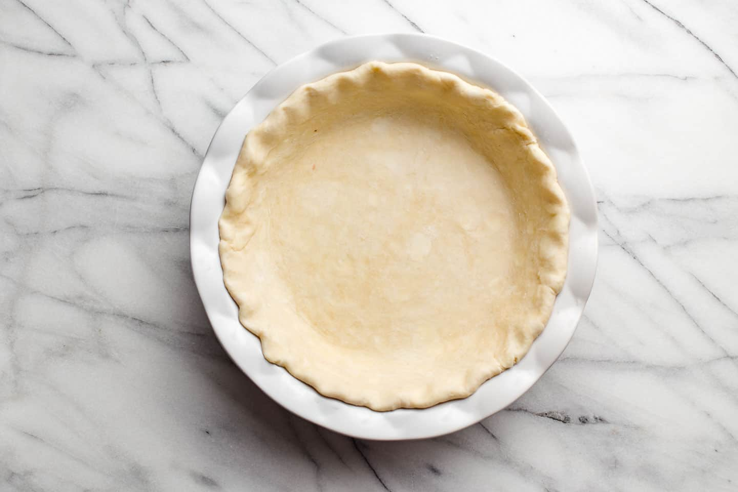 Unbaked all-butter pie crust in a pie plate.