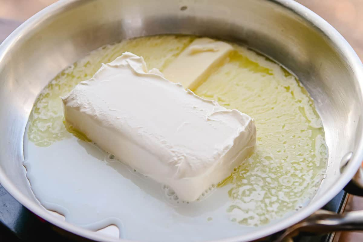 Cream cheese and butter melting in a saucepan.