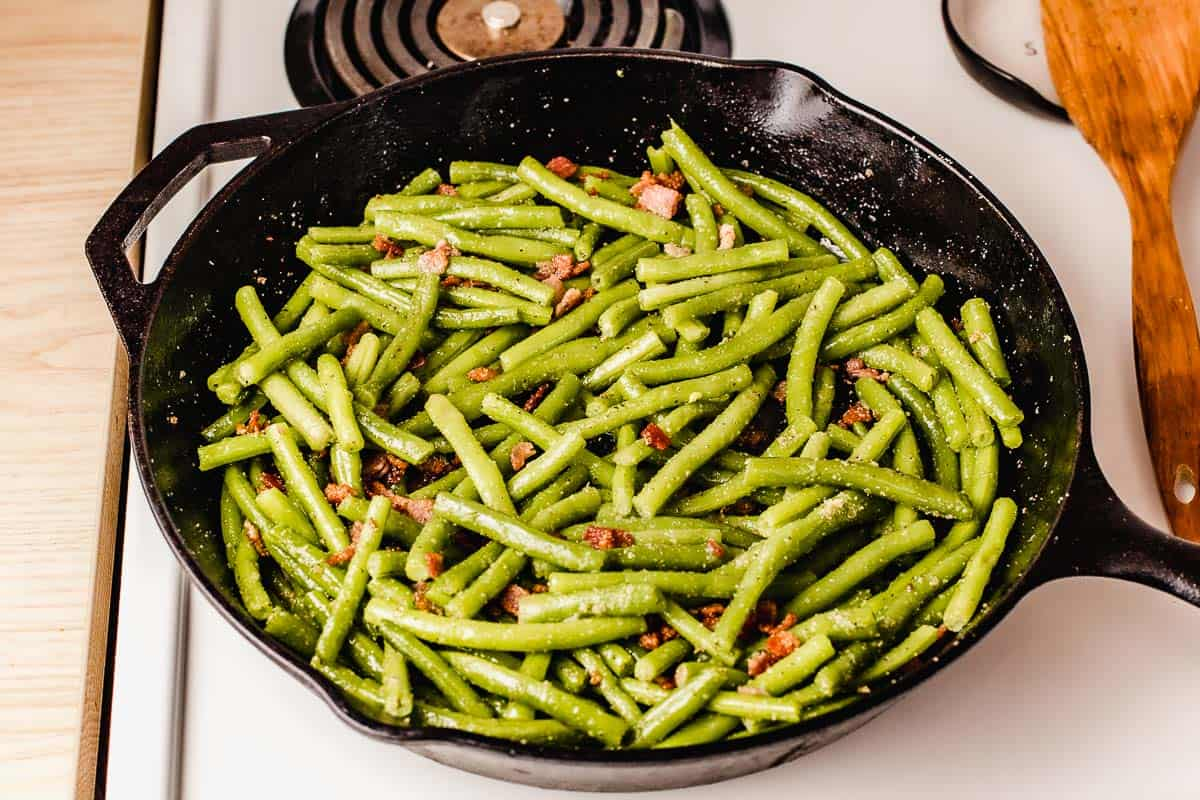 Green beans with bacon cooking in a cast iron skillet.