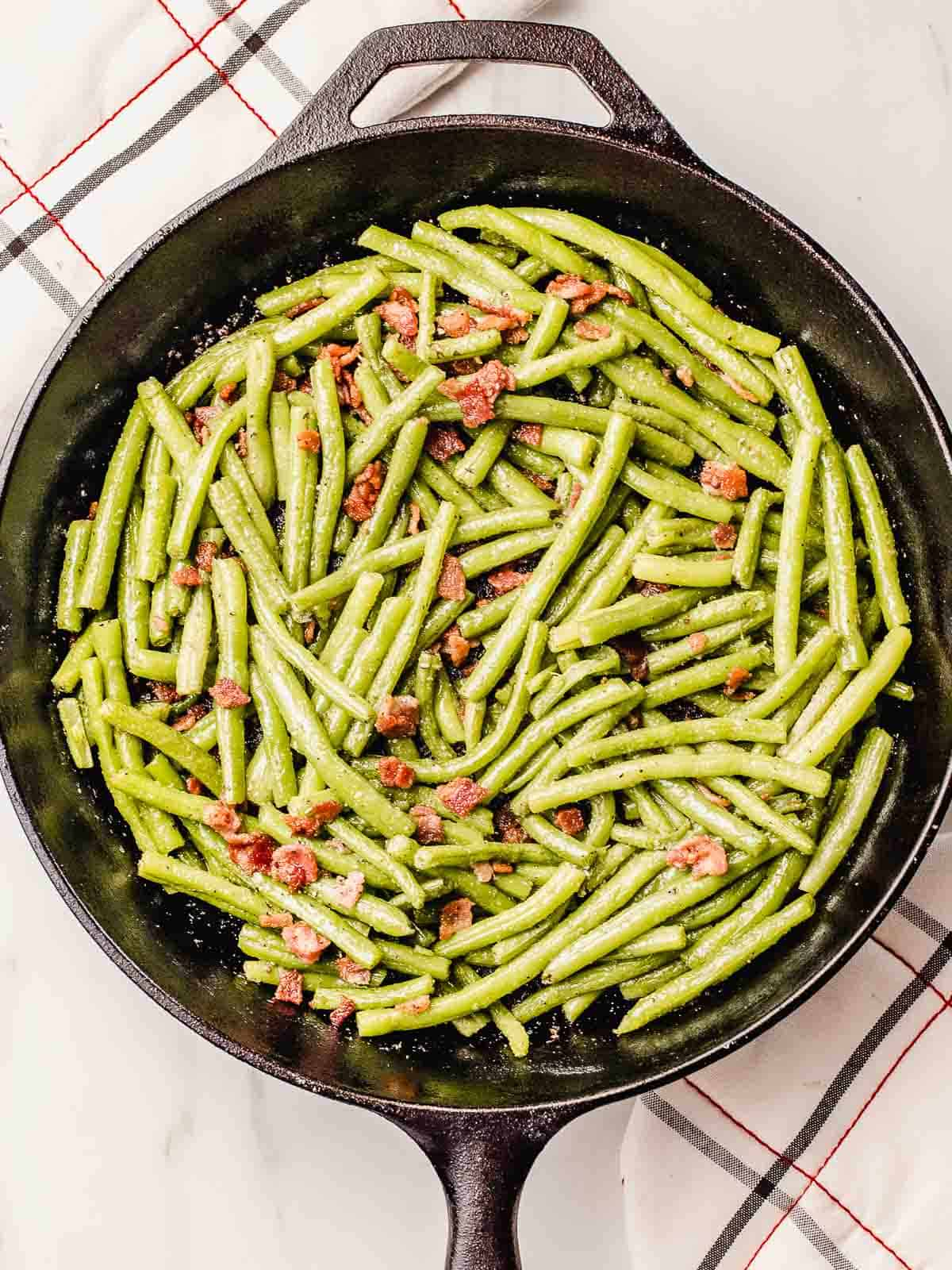 Green beans with bacon in a cast iron skillet.