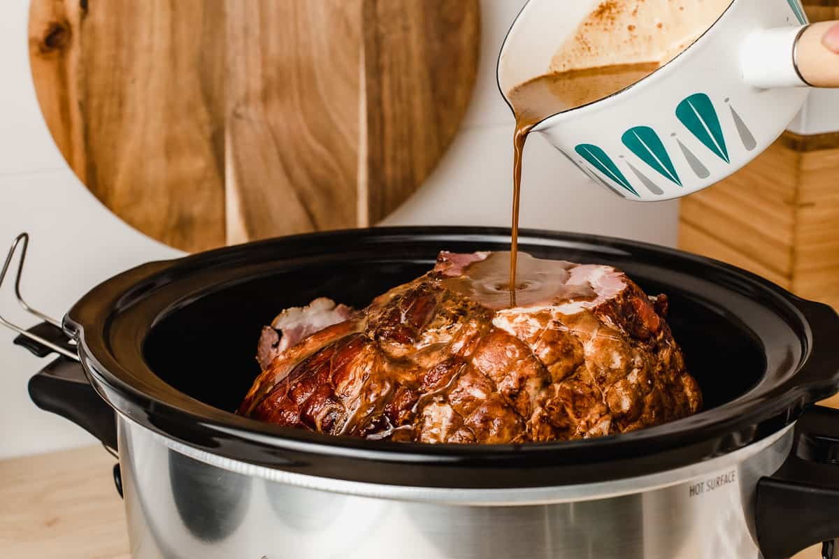 Pouring glaze onto ham in a slow cooker.