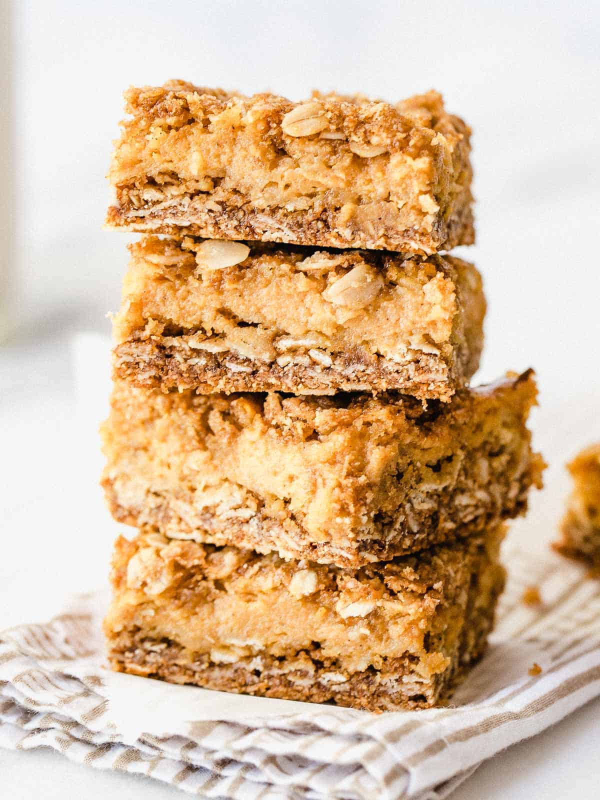 Pumpkin Pie Crumble Bars stacked on top of each other..