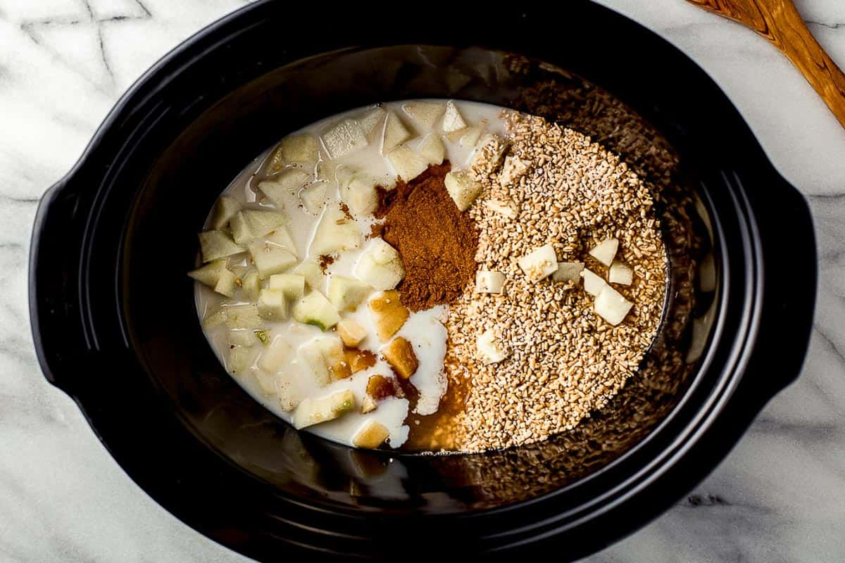 Slow cooker apple oatmeal ingredients in the liner.