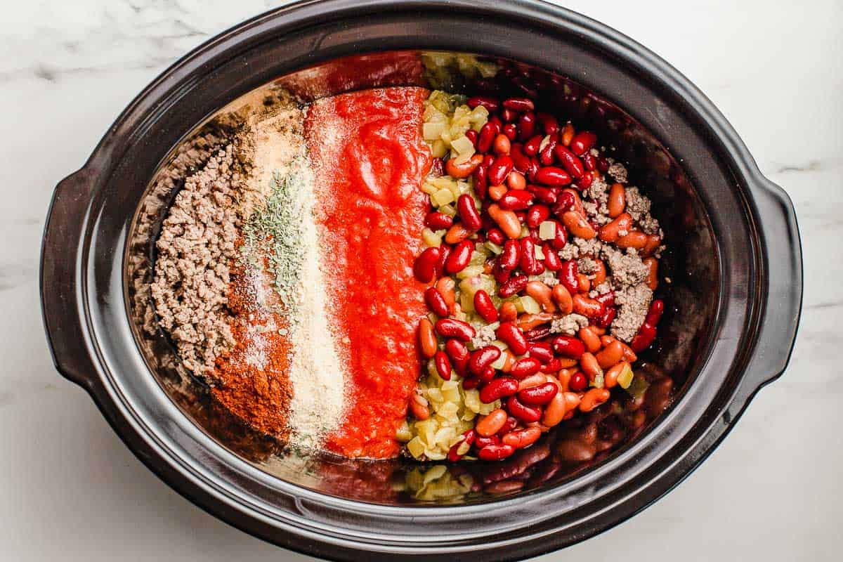 Slow cooker chili ingredients in the liner insert.
